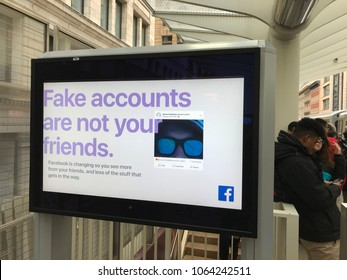 Chicago, Illinois/USA- April 4, 2018. Exterior train stop in Chicago featuring a Facebook ad warning against fake accounts. People nearby wait for the train.