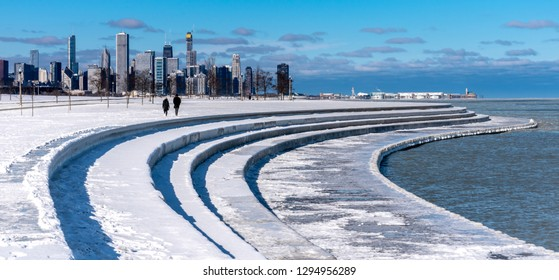 Chicago, Illinois/USA - January 21, 2019:  Beautiful winter scenery looking north towards the Chicago skyline.  Sweeping lines of the walkway are covered with white ice and snow.  Sunny blue sky.