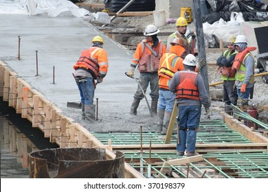 CHICAGO, ILLINOIS/USA â?? January 30, 2016: Hispanic workers finish concrete mix for third phase of Chicago riverwalk construction in Loop.