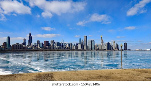 CHICAGO, IL/USA - MARCH 4, 2019:  The Chicago skyline, with a frozen Lake Michigan, with ice reflections.
