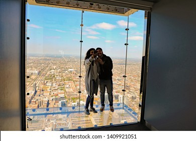 CHICAGO, IL/USA - MAY 15, 2019:  The Skydeck in the Willis Tower is a popular tourist destination for views, and the thrill of heights.  Here is a couple doing a selfie, a trend.