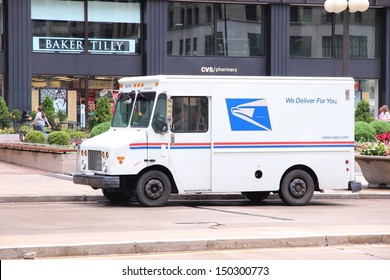 CHICAGO - JUNE 26: People walk past US Postal Service truck on June 26, 2013 in Chicago. USPS is the operator of the largest civilian vehicle fleet in the world.