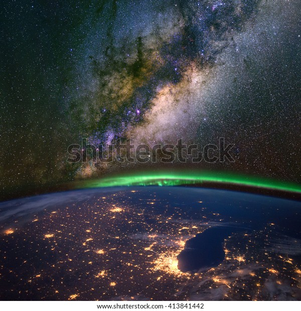 Chicago and lake Michigan from space at night, with the aurora Borealis and the Milky Way. Elements of this image furnished by NASA.