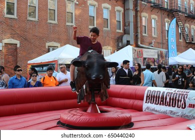 CHICAGO - MAY 27: Boy rides mechanical bull  at Mole de Mayo Festival on May 27 2017 in Chicago. A boy tries to keep his balance on a mechanical bull with one arm raised.