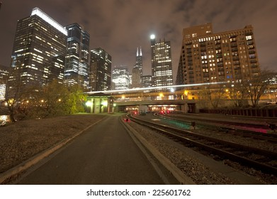 A Chicago railway with a skyline in the back on a dark night.