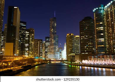 Chicago River with urban skyscrapers and riverwalk at night, IL, USA