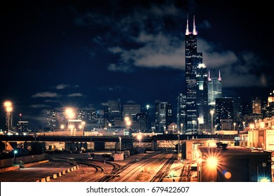Chicago skyline cityscape at night featuring a train yard and urban bridge with a dramatic cloudy sky.