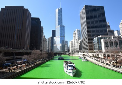 Chicago Skyline cityscape as seen from the Chicago River under a clear blue sky with a green Chicago River on Saint Patrick's Day