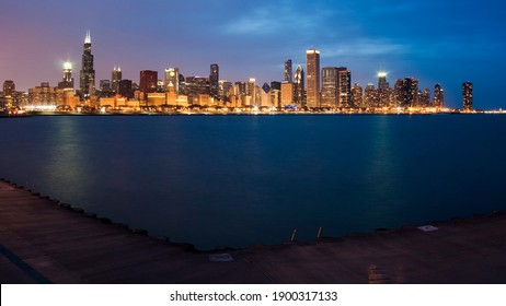 the Chicago skyline at dusk with lake Michigan in foreground