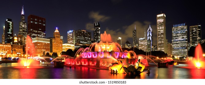 Chicago skyline illuminated at dusk with colorful Buckingham fountain on the foreground