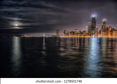 Chicago skyline with Lake Michigan and the moon at night