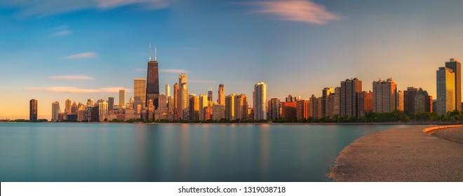 Chicago skyline panorama across Lake Michigan at sunset viewed from North Avenue Beach. Long exposure.