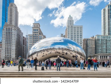 CHICAGO, USA - MARCH 14, 2019: Tourists admire iconic Cloud Gate at Millenium Park during early spring.  Chicago is the third most populous city in the US.