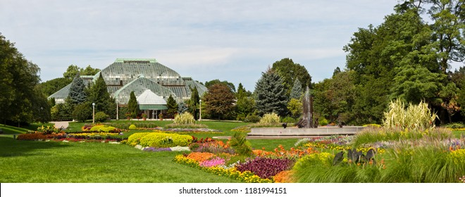 Chicago, USA - September 17, 2018: Conservatory building in Lincoln Park, on a sunny day, surrounded by colorful flowers and plants and green grass.
