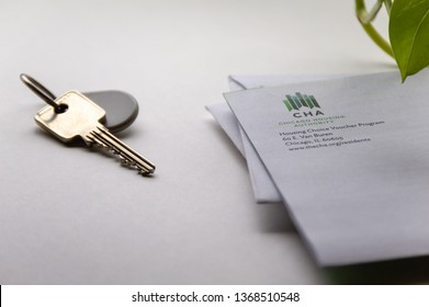 Chicago, USA-April 10, 2019: A letter or mail from Chicago Housing Authority is displayed with a door key and key fob. Public housing assistance program, CHA, Housing and Urban Development.