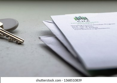 Chicago, USA-April 10, 2019: A letter or mail  from Chicago Housing Authority is displayed with an apartment door key and key fob. Public housing assistance program, CHA, Housing and Urban Development