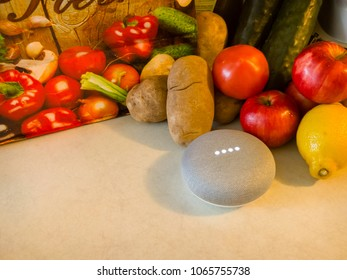 CHICAGO, USA-April 4, 2018. A Google Home Mini is displayed with a delivery of produce on a counter.