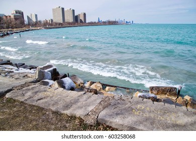 Chicago's magnificent Lake Michigan as seen from the south side looking north during a chilly winter day with splashing waves and skyline on horizon in distance