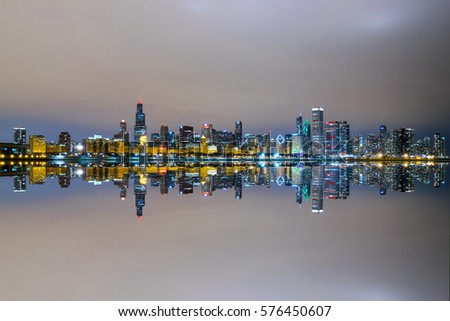 Chicago's Skyline mirrored at night as seen from the Adler Planetarium by Lake Michigan.