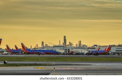 CHICAGO,UNITED STATES - JUNE 5: Southwest Airlines passenger airplanes waiting at terminal on Chicago Midway Airport at sunset. Downtown skyscrapers visible on horizon.