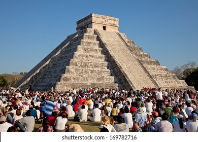 CHICHEN ITZA, MEXICO - MARCH 21: Group of tourists watching the feathered serpent crawling down the temple on Equinox March 21, 2011 in Chichen Itza, Mexico. This is one of the seven wonders of world.