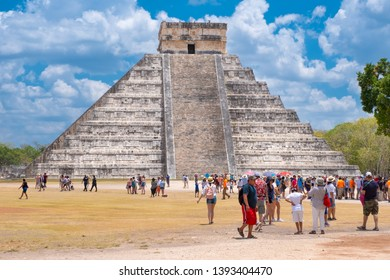 CHICHEN ITZA,MEXICO - APRIL 17,2019 : Tourists next to the Pyramid of Kukulkan on a beautiful day at the ancient mayan city of Chichen Itza