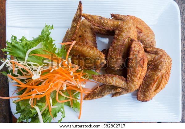 Chichen wing fried with salad in white dish on wooden table