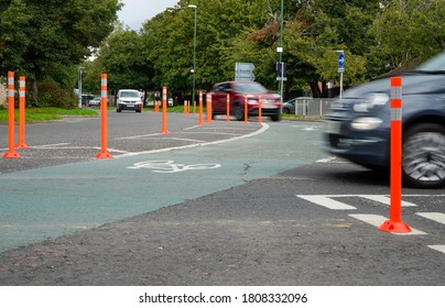 Chichester, Sussex / UK - 2 Sept 2020: Fluorescent orange posts and green road surface mark out a new temporary cycle lane for Covid-19 commuters. A car blurs as it speeds across the junction.