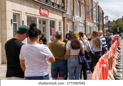 Chichester, Sussex / UK - 20 June 2020: Standing in line at T K Max during Covid-19; nobody wears a mask. Crowd wait behind orange barriers. Focal point on the store front, foreground in soft focus.