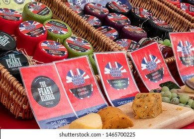 Chichester, Sussex / UK - 28 Jul 2019: Artisan cheddars from the Great British Cheese Company are displayed in wicker baskets on a street market stall. Flavours include Peaky Blinder and Peri Peri.