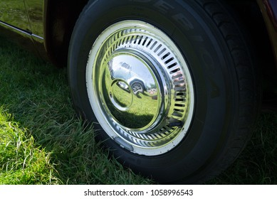 Chichester, United Kingdom - 27 May 2012: A shiny hubcap on a vintage car reflects the adjacent vintage VW Beetle