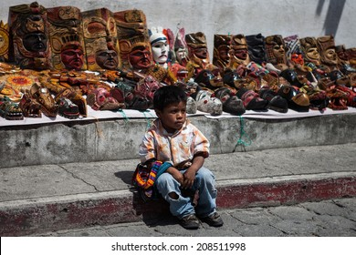 CHICHICASTENANGO, GUATEMALA - MAY 9: Indigenous unidentified boy with carnival masks at Authentic market in Chichicastenango (Chichi), Guatemala on May 9, 2013.