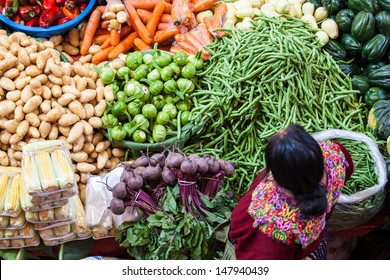 CHICHICASTENANGO, GUATEMALA- MAY 9: An unidentified woman sells vegetables at traditional weekly market in Chichicastenango (Chichi), Guatemala on 9 May 2013