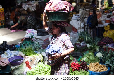CHICHICASTENANGO, GUATEMALA- MAY 9: An unidentified woman sells vegetables at traditional weekly market in Chichicastenango (Chichi), Guatemala on 9 May 2013.