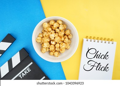 Chick flick movie concept. Popcorn in a bowl and clapperboard on yellow and blue background. Flat lay view.