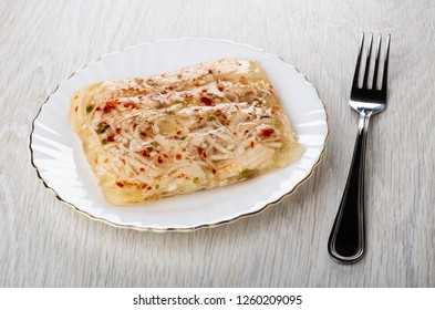Chicken aspic in white glass plate and fork on light wooden table