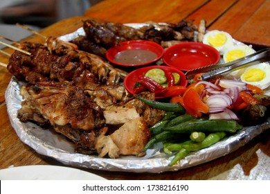 Chicken Ati-Atihan, a traditional grill chicken from Kalibo, Philippines. It served with onions, vegetables, eggs and sauce dips.