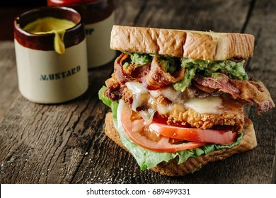 Chicken and Avocado BLT sandwich with mustard and ketchup bottles