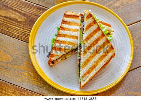 Chicken and avocado wholegrain bread sandwich triangles above view on wooden table
