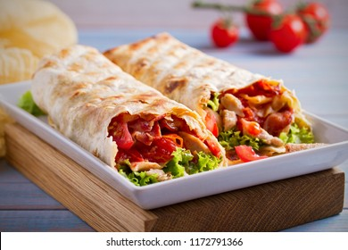 Chicken bacon wraps with tomatoes, lettuce and cheese. Tortilla, burritos, sandwiches twisted rolls. horizontal
