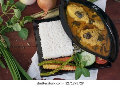 chicken basil is ayam kemangi, is an indonesia traditional food made from chicken soaked with herb and spices, presenting with rice, bean sprouts, tomato, cucumber, carot and long beans