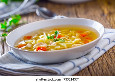 Chicken or beef broth with noodles carrot and parsley in white bowl.