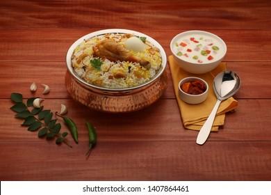 chicken biriyani- chicken dum biriyani in south indian style with wooden brown background - Shutterstock ID 1407864461