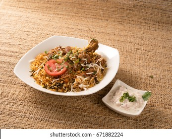 chicken biriyani served in a white plate with raita on banana fiber background