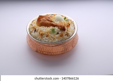chicken biriyani-dum biriyani placed in a brass vessel in south indian style with white background