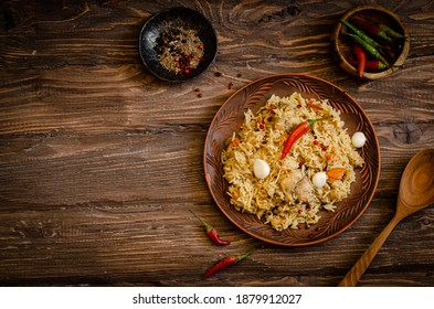 Chicken Biryani. Rice pilaf with Chicken, garlic and chili pepper in clay plate on wooden backgraund. Ramadan food. Indian cuisine. Selective focus. Toned image - Shutterstock ID 1879912027