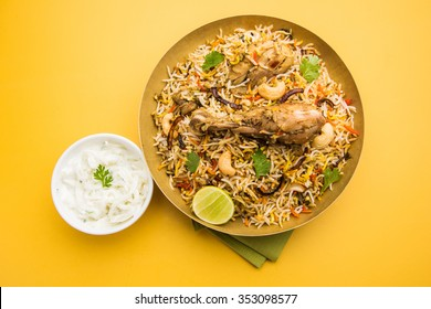 Chicken Biryani showing leg piece - It's a delicious recipe of Basmati rice mixed with with spicy marinated chicken in a bowl. Served with Salan or Raita. served in a bowl or plate. Selective focus