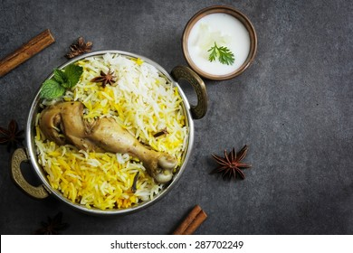 Chicken Biryani with yogurt dip on beautiful moody background with copy space,overhead view