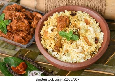 Chicken biryani/Hyderabadi Biriyani/ fried rice and chilli chicken curry, Kerala India. Popular traditional dish/food made using basmati/saffron/jasmine rice, various other exotic Indian spices/masala
