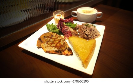 Chicken black pepper steak grill set has brown rice, lettuce, custard, mushroom cream soup, butter bread cheese toast in plate are put on wooden desk and black color fade in, Focus select at center.